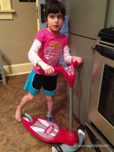 Wearing her brother's clothes on her new scooter!
